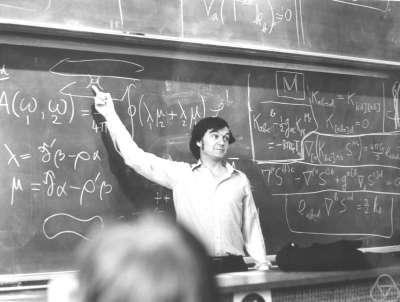 Sir Roger Penrose en train d'expliquer le pont d'Einstein-Rosen avec la théorie des spineurs en 1988 à l'Université de Durham. Il fut l'un des premier à étudier la formation d'un trou noir lors de la collision de particules à haute énergie. Crédit : Mathematisches Forschungsinstitut Oberwolfach.