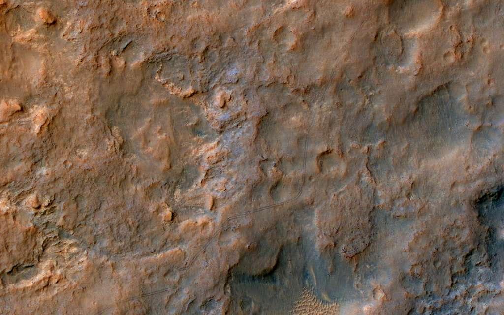 Sur cette photographie réalisée par la caméra HiRise de l'orbiteur MRO, on peut voir les traces laissées dans le sillage du rover Curiosity au cours de son périple qui le rapproche des flancs du mont Sharp. Cliquez sur l'image pour l'agrandir et observer les fines traces noires. © Nasa, JPL-Caltech