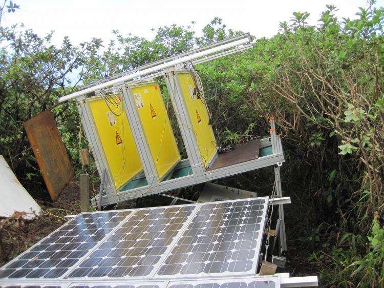 Ceci est un télescope pour volcanologues. Les trois surfaces planes de couleur jaune sont des détecteurs de muons. Cet instrument, alimenté par énergie solaire, a été installé sur le flanc de la Soufrière. © CNRS