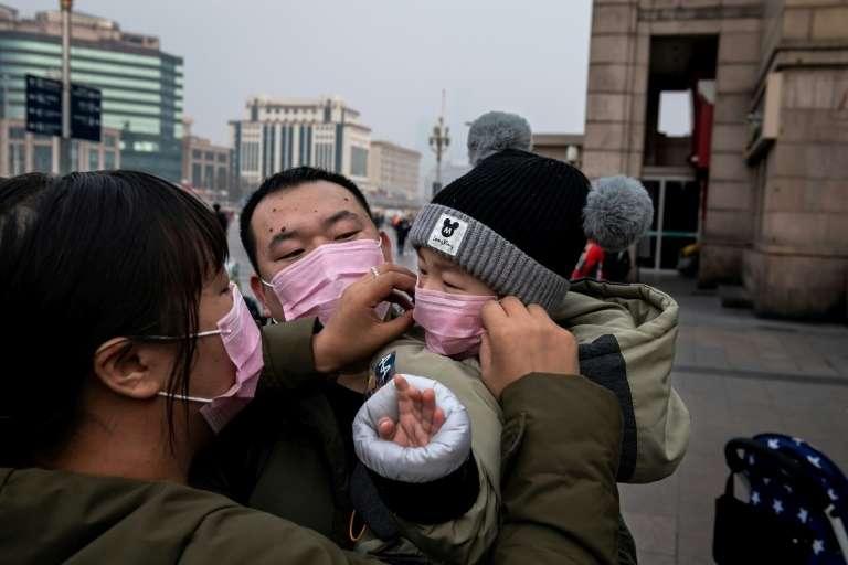Devant la gare de Pékin, une famille revêt des masques de protection. © Nicolas Asfouri, AFP