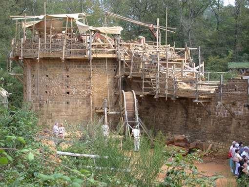 Vue nord-est : tour maîtresse en cours de restauration. Terminée elle fera 30 mètres. Au pied de la tour, on aperçoit la cage à écureuil (engin de levage) qui permet de monter pierres et mortier sur la tour en construction. © Guédelon - Reproduction et utilisation interdites - Tous droits réservés