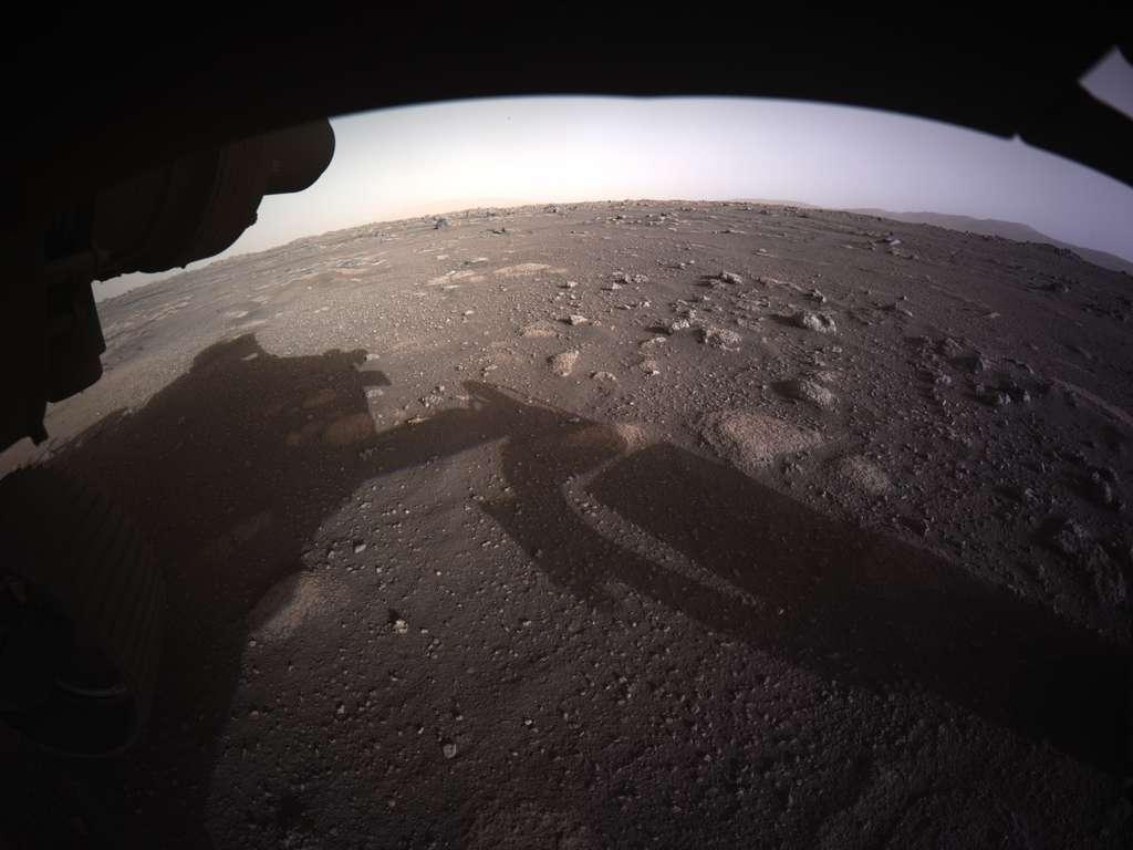 Première image en couleur du site d'atterrissage de Perseverance acquise par le rover de la Nasa quelques instants après son atterrissage. Pour les scientifiques, ce paysage présente de nombreuses caractéristiques intéressantes dont des blocs rocheux enterrés et des cailloux d'une très grande variété de taille. À l'horizon, on distingue ce qui est certainement le rempart du cratère. © Nasa/JPL-Caltech