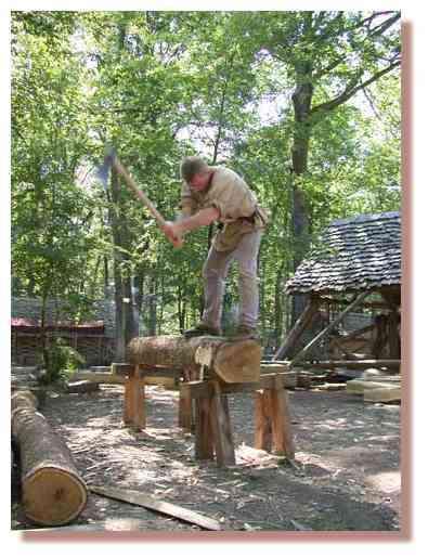 Bûcheron en train d'équarrir ( = rendre quadrangulaire ) un fût de chêne © Photo Guédelon.
