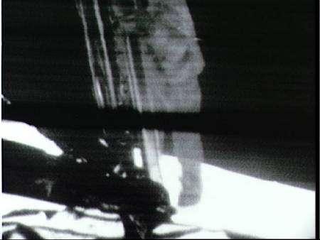 Neil Armstrong, filmé par la caméra fixée sur le LM, descend l'échelle. © Nasa