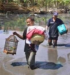 Deux habitants progressent dans la vase pour fuir la zone du sinistre (Crédits : TRISNADI/AP/EMPICS)