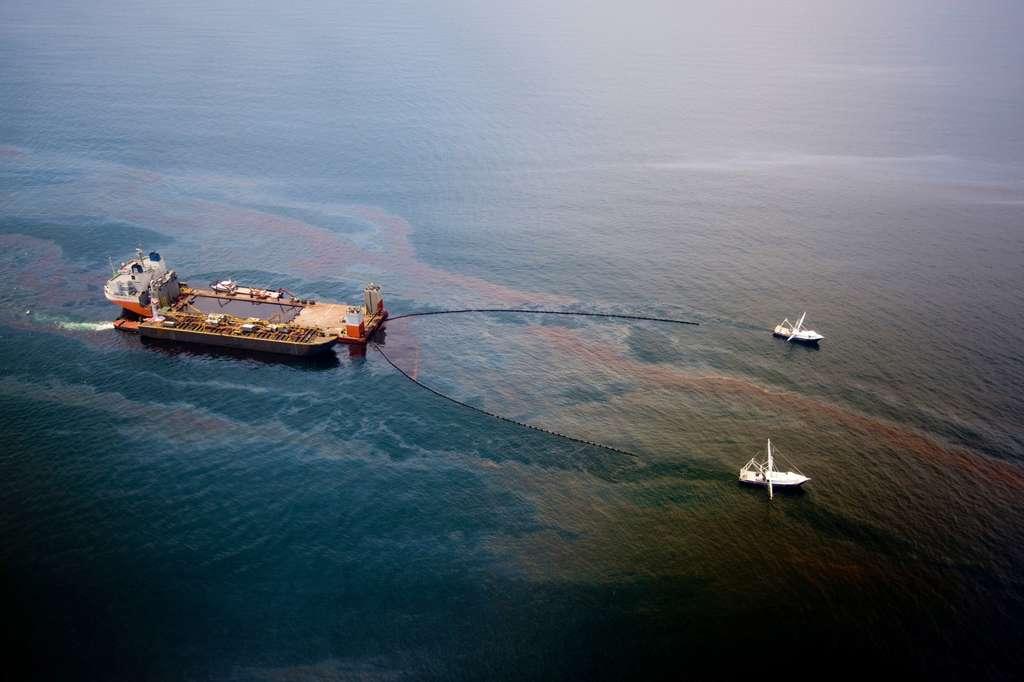Le Mighty Servant 3, avec deux autres bateaux, en train de récolter le pétrole d'une nappe, le 18 juin 2010. Au total, environ 120 millions de litres ont été récupérés. Ce type de pollution est clairement visible. L'entrée de molécule cancérigène dans les chaînes alimentaires l'est mois. © BP