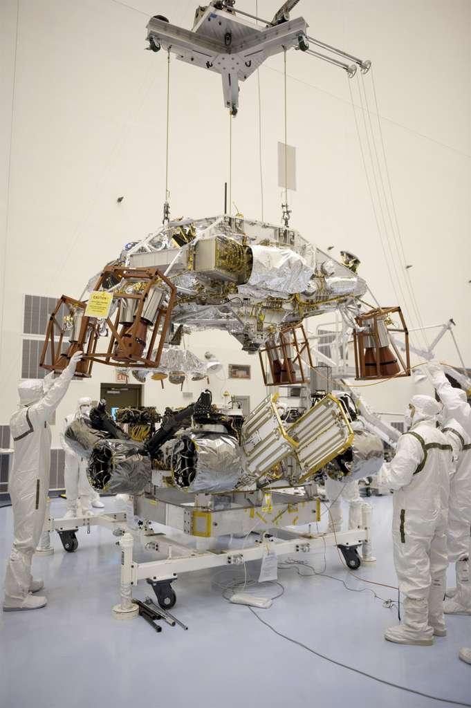 À gauche, l'innovant système d'atterrissage Skycrane, qui doit devenir la norme pour se poser sur Mars, en cours d'installation sur le rover Curiosity. À droite, installation du cône arrière du bouclier (backshell en anglais), qui abrite également les parachutes. © Nasa/JPL-Caltech