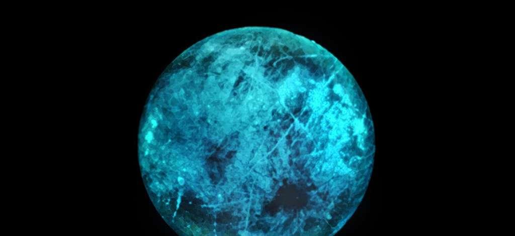 Cette illustration de la lune de Jupiter, Europe, montre comment sa surface glacée peut briller sur sa face nocturne, le côté opposé au Soleil. Les variations de la lueur et de la couleur de la lueur elle-même pourraient révéler des informations sur la composition de la glace à la surface d'Europe. © Nasa, JPL-Caltech