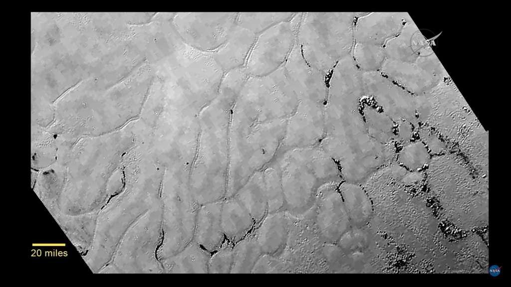 La plaine glacée de Pluton baptisée Spoutnik intrigue. On y voit des sillons séparer la surface de glace en zones de 20 à 40 km de large et abritant par endroits des amas de matières sombres. © Nasa/JHUAPL/SWRI