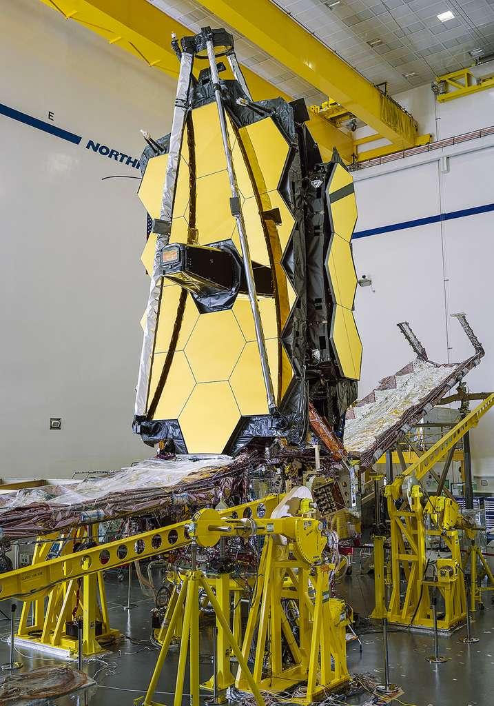 Vue de profil du télescope spatial James Webb. Le bouclier thermique est clairement visible (la structure horizontale sous le miroir). Quant aux miroirs, le primaire est ici vue en position replié et le miroir secondaire, également replié est en haut de l'image. © Nasa, Chris Gunn
