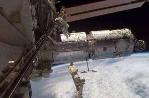 Harmony à poste, en attente de Columbus. Le corps de l'ISS est à gauche. Sous l'astronaute, le laboratoire américain Destiny, y est fixé. A droite, le nœud de jonction Harmony, qui porte, à son extrémité droite, le connecteur PMA-2. C'est au niveau de la porte circulaire que l'on distingue sur Harmony que sera installé Columbus. En face de lui, de l'autre côté du cylindre, une ouverture identique accueillera Kibo, le laboratoire japonais. © Nasa