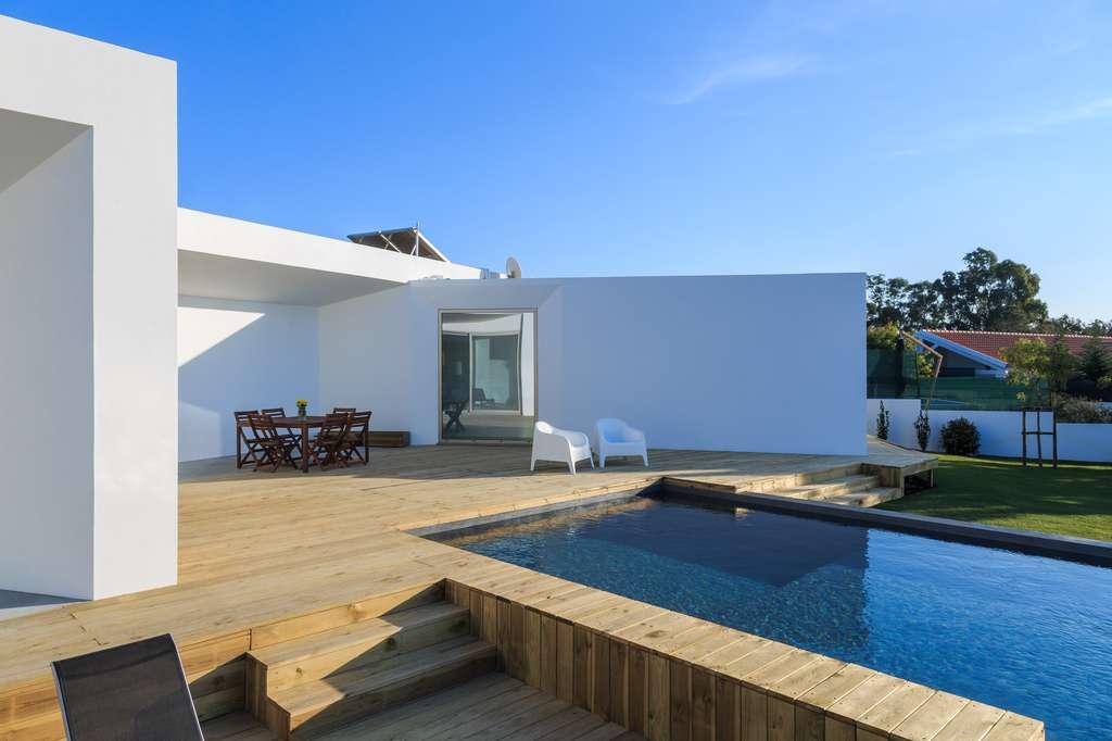 Une piscine hybride ou semi-enterrée est particulièrement esthétique, permettant d'aménager une plage autour de l'espace de baignade ou des douches d'extérieur. © Luis Viegas, Fotolia