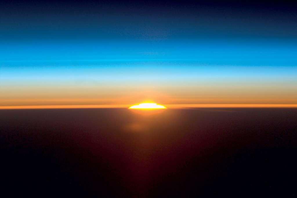 Photographie de l'atmosphère au lever du Soleil réalisée par un équipage de la Nasa, depuis la Station spatiale internationale en juin 2011. Compte tenu de l'échelle, les couches bleutées représentent la stratosphère, où une strie de couleur bleue plus intense correspond à la couche d'ozone. Les couches rougeâtres au-dessus du sol encore non éclairé représentent la troposphère. © Nasa