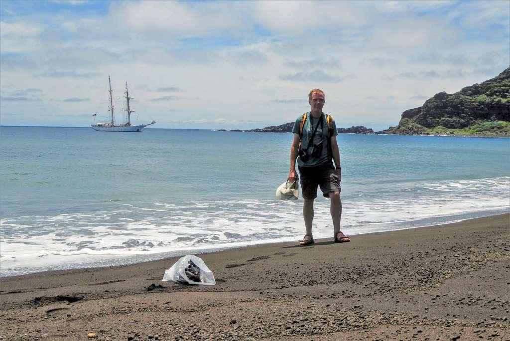 Dan Slayback du Nasa Goddard Space Flight Center sur une plage de Hunga Tonga-Hunga Ha'apai en octobre 2018. En arrière-plan, le SSV Robert C. Seaman, voilier océanographique de la SEA Education Association (SEA). © Dan Slayback