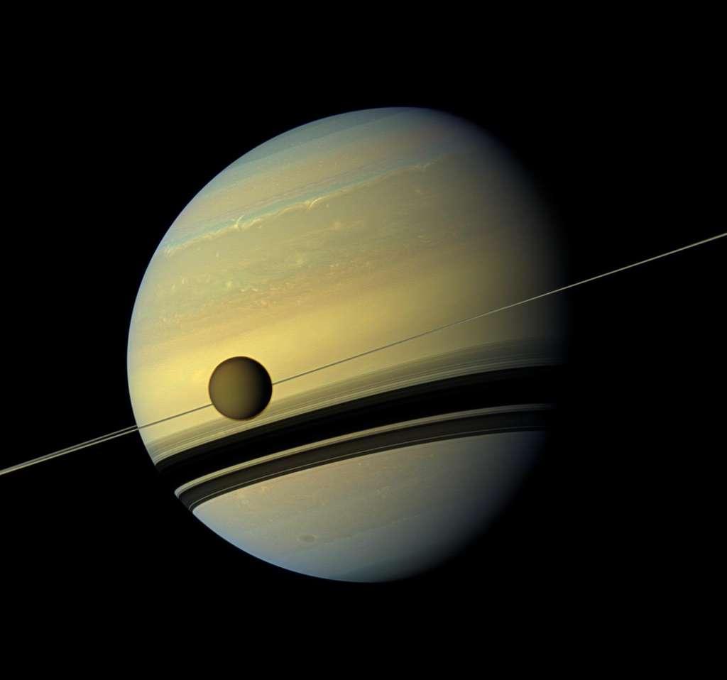 Sur cette image prise par Cassini, on voit Titan au premier plan. Les traces de terribles tempêtes en 2011 sont à peine visibles au second plan dans l'hémisphère nord de Saturne. © Nasa