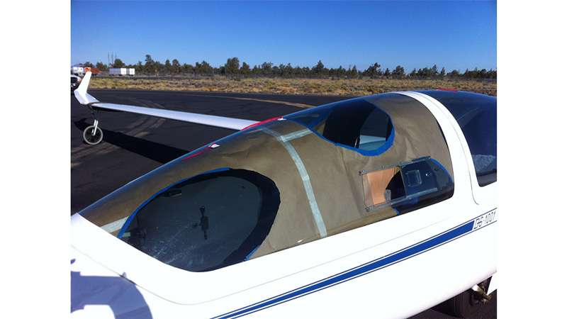 Un essai d'obstruction par du papier Kraft de la verrière d'un planeur classique pour simuler les hublots du modèle Perlan 2. © DR