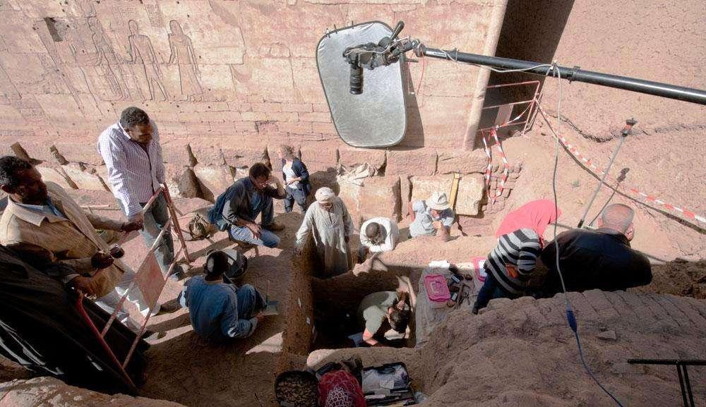 Les archéologues au mois de décembre 2014, en plein travail à l'est du temple de Ptah à Karnak. Ils déterrent des objets jetés pêle-mêle dans une fosse, autour de la partie inférieure d'une statue en calcaire du dieu Ptah. © CFEETK, CNRS