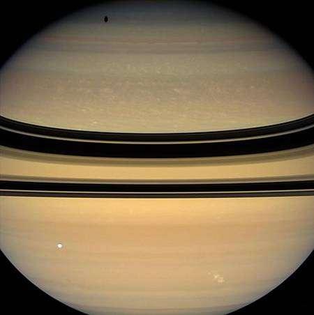 Cette image prise le 29 avril 2008 depuis une distance de 1,7 million de km a aussi été réalisée en combinant les filtres rouge, vert et bleu de la caméra grand angle de Cassini et est fidèle à la réalité telle que l'apercevrait l'œil humain. Résolution : 94 km/pixel. Le satellite Tethys (1.071 kilomètres de diamètre) apparaît sous la forme d'un disque clair et projette son ombre sur l'hémisphère nord de la planète. Crédit : Nasa/JPL