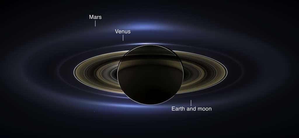 Saturne devant le Soleil, en contre-jour. Sur cette image composite réalisée le 19 juillet 2013, on distingue trois planètes, dont la nôtre (Earth, en anglais sur l'image), au sein de la lueur des anneaux. Il faisait jour et beau en Europe ce jour-là. Beaucoup d'entre nous sont donc sur cette image. André Brahic aimait dire qu'il montrait cette image en tant que photo d'identité. © Nasa, Caltech, SSI