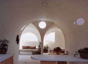 L'intérieur d'un écodôme, version luxueuse. Un enduit interne a été appliqué sur les sacs de terre. On remarque que l'ouverture au sommet rend ces habitations très lumineuses. © Association Cal-Earth