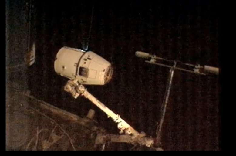 Le bras Canadarm2, commandé par deux astronautes installés dans la coupole, s'approche de la capsule Dragon pour l'accrocher. © Nasa TV