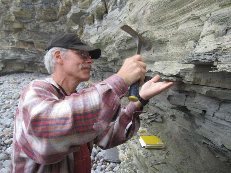Paul Olsen, l'un des coauteurs de l'étude, récupère des roches basaltiques datant de la fin du Trias sur des falaises maritimes du sud de la Grande-Bretagne. Leur datation est précise, elles ont environ 201.564.000 ans. Les épanchements magmatiques qui ont créé ces roches auraient causé la disparition d'une espèce sur deux sur Terre. © Kevin Krajick, Earth Institute