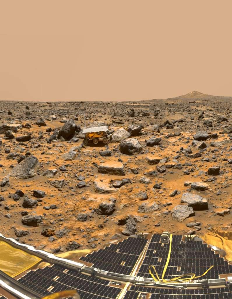 Le site où s'est posé Pathfinder (on aperçoit un de ses panneaux solaires au premier plan) en 1997. À quelques mètres de là, dans la plaine jonchée de débris, le petit rover Sojourner, premier astromobile à gambader sur Mars. © Nasa, JPL