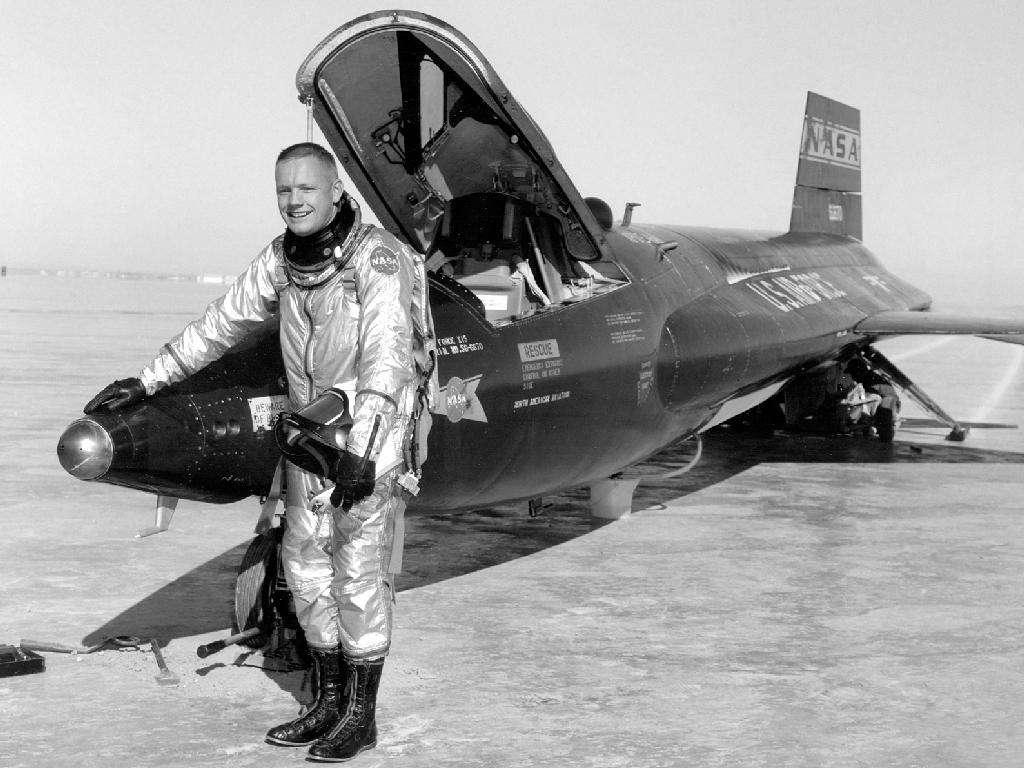 Neil Armstrong à côté d'un des avions-fusées X-15 qu'il a pilotés. Le North American X-15 était un avion-fusée expérimental américain, construit dans le cadre d'un programme de recherche sur les vols à très haute vitesse et très haute altitude. © Nasa