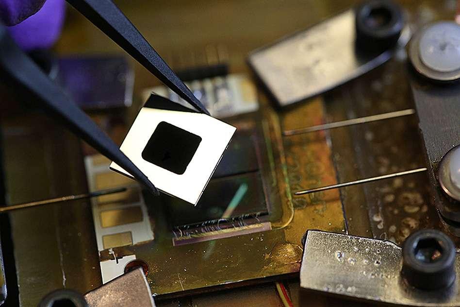 Au centre du carré blanc se trouve l'équipement nanostructuré qui a été développé au MIT pour absorber toute l'énergie du spectre solaire, afin de la convertir en chaleur puis en rayonnement thermique. Le récepteur se compose de nanotubes de carbone, tandis que l'émetteur intègre des cristaux photoniques omnidirectionnels Si/SiO2. En dessous se trouve une cellule photovoltaïque au silicium. © John Freidah