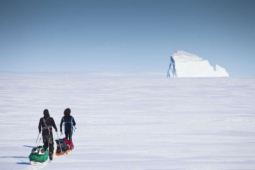 Julien Cabon et Alan Le Tressoler progressent sur la banquise, en 2011, le long de la côte est du Groenland. Devant eux, un iceberg de plus d'une trentaine de mètres de hauteur. © Raphaël Demaret