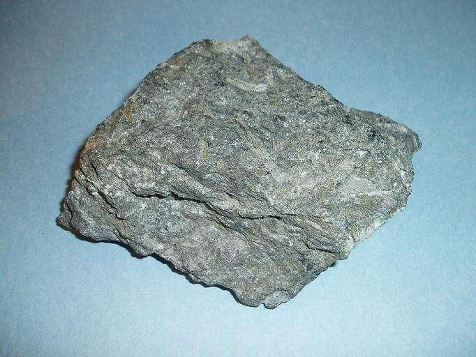 Un échantillon de komatiite de 9 cm de long trouvé au Canada. Sur Terre la komatiite est une roche volcanique ultramafique très rare à olivine et pyroxène tirant leur nom de la rivière Komati, en Afrique du Sud. La plupart des komatiites sont vieilles de plus de deux milliards d'années. Leur formation implique des températures de fusion de l'ordre de 1.600 à 1.650 °C contrairement aux 1.250 à 1.350 °C des basaltes actuels. © Wikipédia, DP
