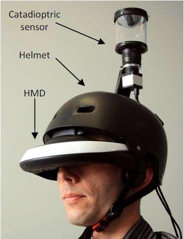 Le prototype du FlyViz avec au sommet la caméra panoramique (catadioptric sensor) pointée vers un miroir hyperbolique montée sur un casque de protection classique (helmet). L'utilisateur visionne l'image à 360° dans le casque à affichage tête haute (HMD ou head mounted display). © Inria, Esiea, Insa