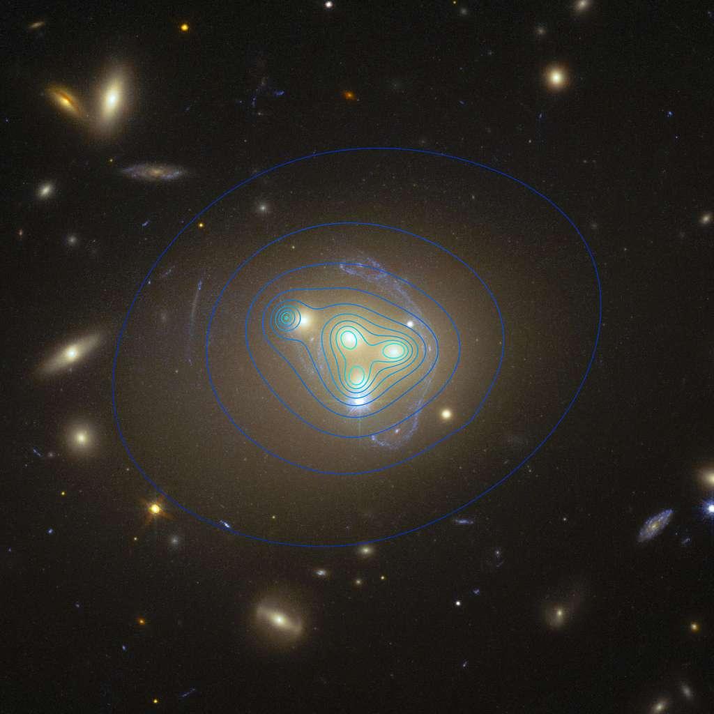Un zoom sur la collision de quatre galaxies étudiée par les astronomes fourni par le télescope Hubble. Les lignes bleues indiquent la répartition et la densité de matière noire. Ces arcs entourant les galaxies sont produits par un effet de lentille gravitationnelle forte. Pour trois galaxies, les concentrations de matière noire coïncident bien avec celle la matière visible. Mais pour la quatrième, à gauche, les deux sont nettement décalées. © ESO/R. Massey