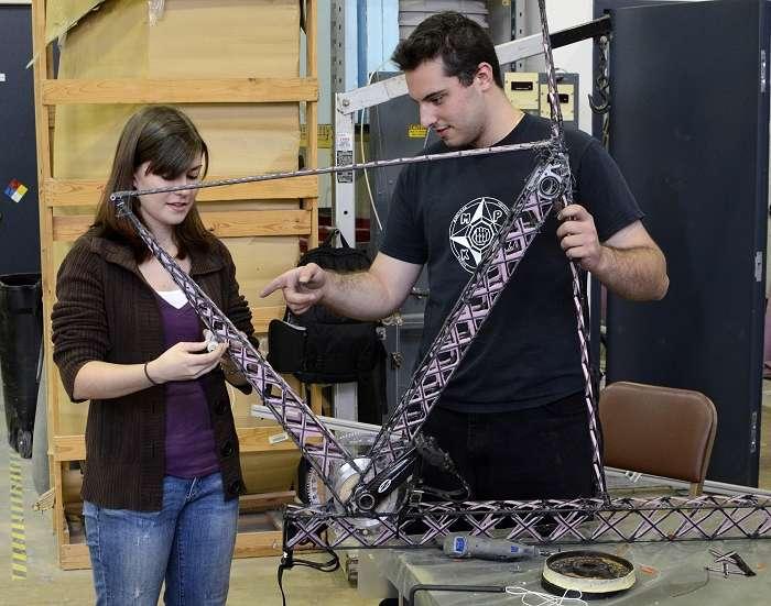 Jill Ferrick et Panagiotis Koliais assemblent les minuscules poutres en fibres de carbone qui constitueront le cockpit du Gamera II. Le pédalier inférieur est déjà en place. L'emplacement pour celui du haut, manœuvré avec les bras, est visible à côté de la main gauche de l'étudiant. © University of Michigan/Department of Aerospace Engineering
