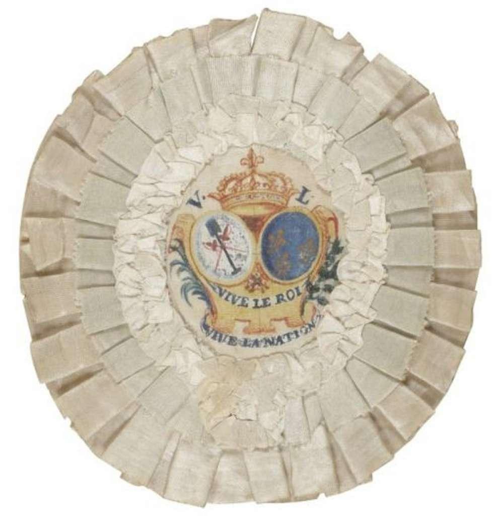 """Cocarde royaliste blanche pour chapeau (le bleu est présent avec les armoiries """"d'azur semé de fleurs de lis d'or"""") ; inscription """"vive le roi, vive la nation"""", diamètre 12 cm, soie blanche, 1790. © ADER NORDMANN."""