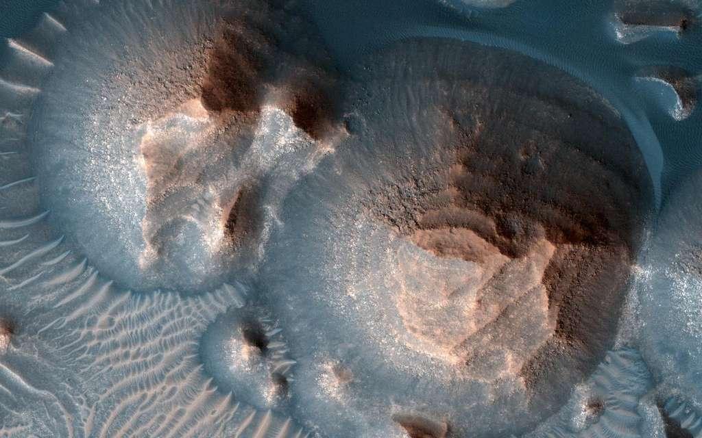 Ici, plusieurs cratères de volcans dans la région martienne d'Arabia Terra. Une image prise par la High Resolution Imaging Experiment embarquée à bord de Mars Reconnaissance Orbiter (MRO, Nasa). Les cratères sont remplis de roches stratifiées, souvent exposées dans des monticules arrondis. Les couches brillantes ont à peu près la même épaisseur, ce qui les fait ressembler à des marches d'escalier. Le processus qui a formé ces roches sédimentaires n'est pas encore bien compris. Elles auraient pu se former à partir de sable ou de cendres volcaniques soufflées dans le cratère ou dans l'eau si le cratère abritait un lac. © Nasa, JPL-Caltech, Université de l'Arizona