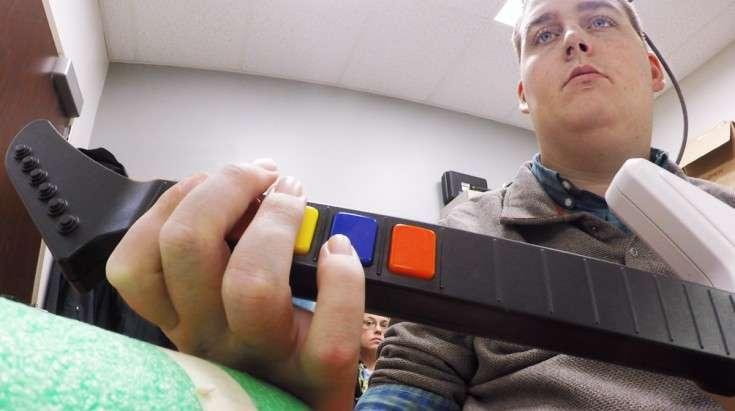 Après de longs mois d'entraînement, Ian parvient à accomplir des gestes complexes et même à jouer à Guitar Hero ! © Ohio State University Wexner Medical Center, Battelle
