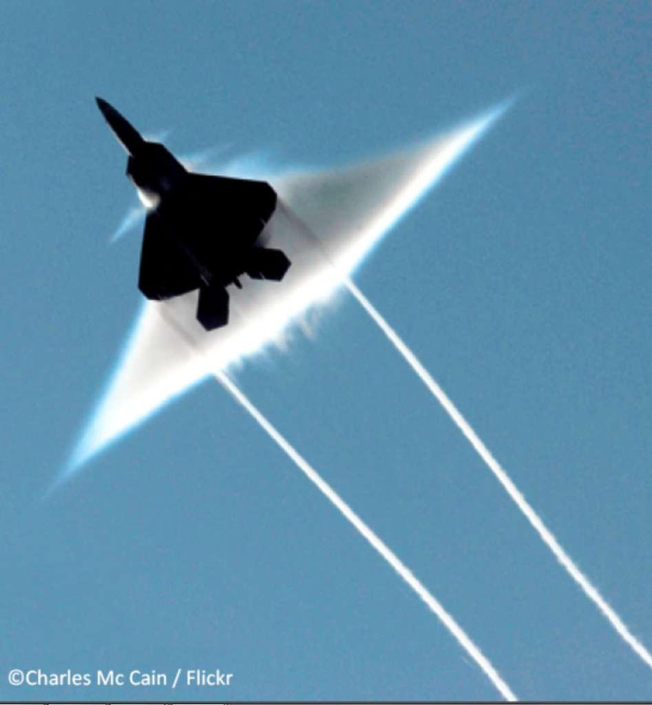 Photographie d'un avion F-22 Raptor de l'armée de l'air américaine en vol supersonique, réalisée depuis le porte-avions USS John C. Stennis. La condensation de l'eau forme des nuages qui servent de marqueurs des zones en dépression. Le nuage triangulaire principal représente le cône de Mach le plus important, formé à partir du bord d'attaque de l'aile. On note aussi les traînées nuageuses où se condense la vapeur d'eau issue des réacteurs situés près des extrémités des ailes. © Charles Mc Cain, Flick, cc by nc 2.0