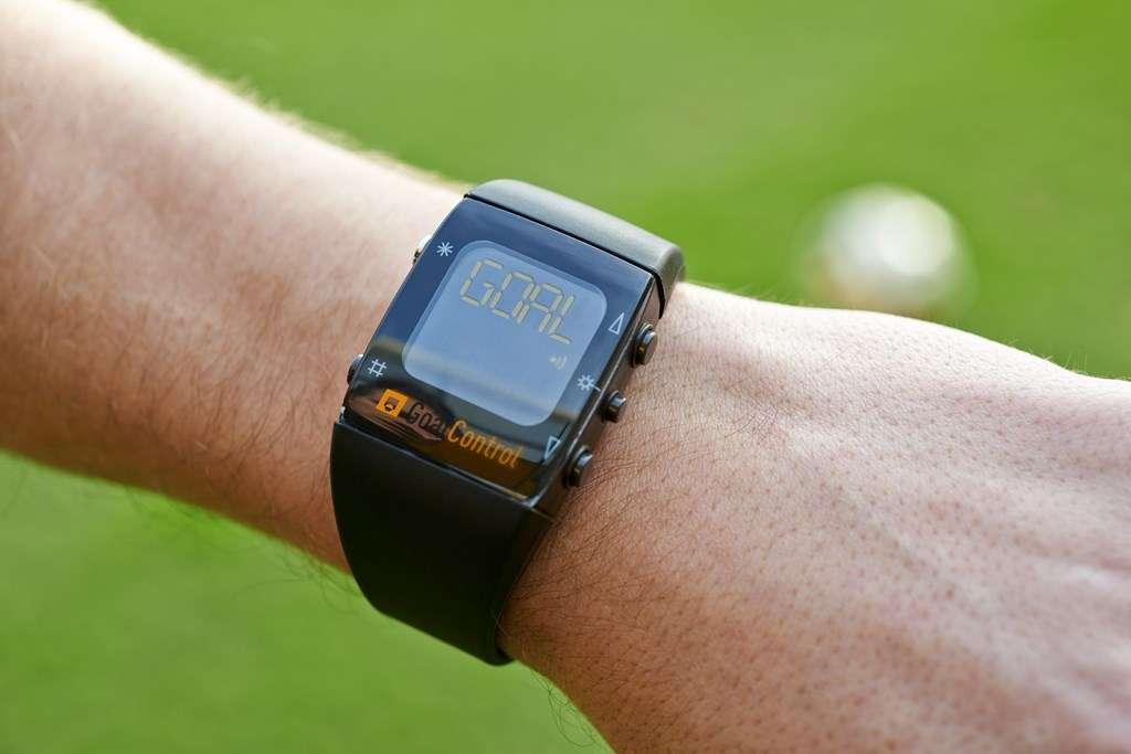 Avec Goal-line, l'arbitre porte une montre connectée avec le système d'analyse GoalControl-4D. Si le ballon passe la ligne de but, un signal radio protégé par chiffrement est envoyé depuis les serveurs. La montre émet une vibration et affiche le mot« goal » sur l'écran pour confirmer le but. © GoalControl