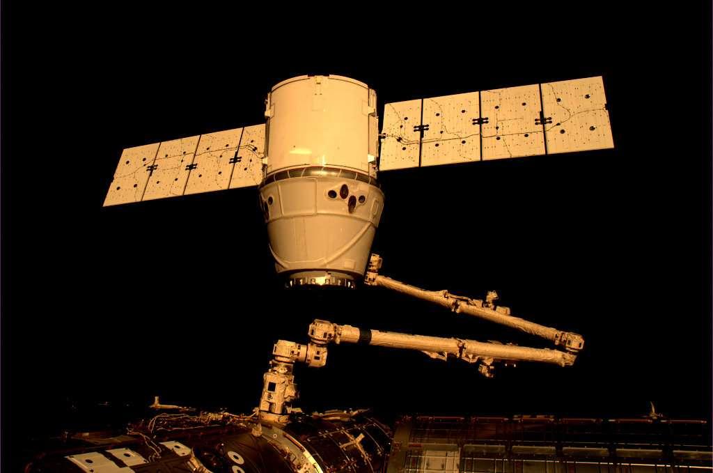 Le bras est en train de se replier pour apporter la capsule Dragon, un engin de 3,70 m de diamètre, sans les panneaux solaires. © André Kuipers/Esa/Nasa