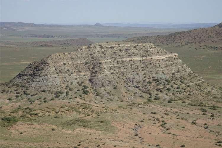Les chercheurs ont daté les dépôts de cendres de cette colline, appelée koppie, dans le bassin du Karoo, en Afrique du Sud. La partie inférieure de koppie Loskop expose des strates d'avant l'extinction du Permien final (Formation de Balfour), tandis que la partie supérieure contient des couches déposées après l'extinction (Formation de Katberg). © John Geissmande
