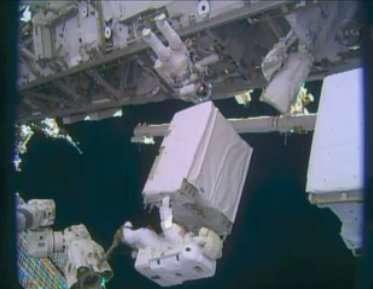 Rick Mastracchio (en haut) et Mike Hopkins (en bas, installé sur le bras robot) ce mardi 24 décembre 2013 en train de placer la nouvelle pompe, d'une masse de 350 kg. En orbite, donc en apesanteur, le poids est nul mais l'inertie, elle, est toujours là. © Nasa