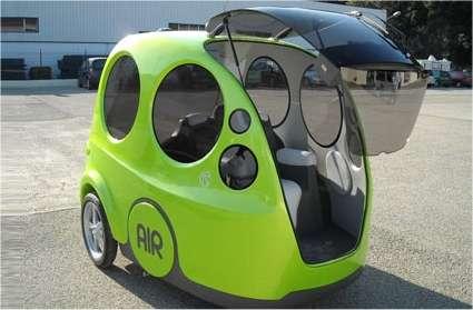 Une allure curieuse et plutôt amusante pour l'Airpod, dont le conducteur entre par la portière avant, ici grande ouverte. Il trouvera un joystick pour piloter l'engin tandis que ses passagers entreront par l'arrière et lui tourneront le dos. On remarque les grandes roues arrière. Celles de l'avant, directrices, sont minuscules et mécaniquement réunies, ce qui évite un train avant lourd et complexe. © MDI