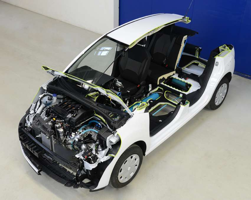 La 2008 Hybrid Air de PSA. Sous le capot, le petit moteur à essence (à gauche sur l'image) est décentré. Une pompe, sous les tuyaux bleus, reçoit ou envoie l'huile du système hydraulique, entraînant un moteur, situé juste à côté. Les roues sont entraînées par ces deux moteurs, séparément ou ensemble. On distingue, en bleu, le réservoir d'air comprimé sous l'habitacle et, de la même couleur, le réservoir d'huile dans le coffre arrière, chargé de transmettre la basse pression au moteur. © PSA