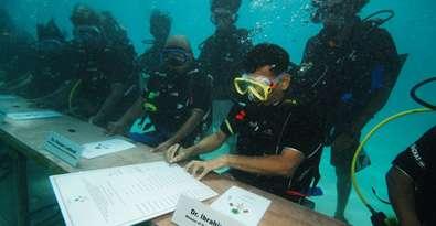 Le 17 octobre 2009, le gouvernement des Maldives se réunit symboliquement sous l'eau. Le président Nasheed signait l'appel à lutter contre les émissions de CO2 qui conduisent à élever le niveau des mers, menaçant la survie des sociétés vivant sur des îles peu élevées. © The President's Office, République des Maldives