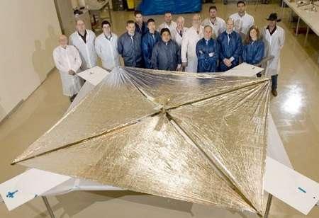 Lors d'un test de déploiement en laboratoire, l'équipe du projet pose devant NanoSail-D. © Nasa