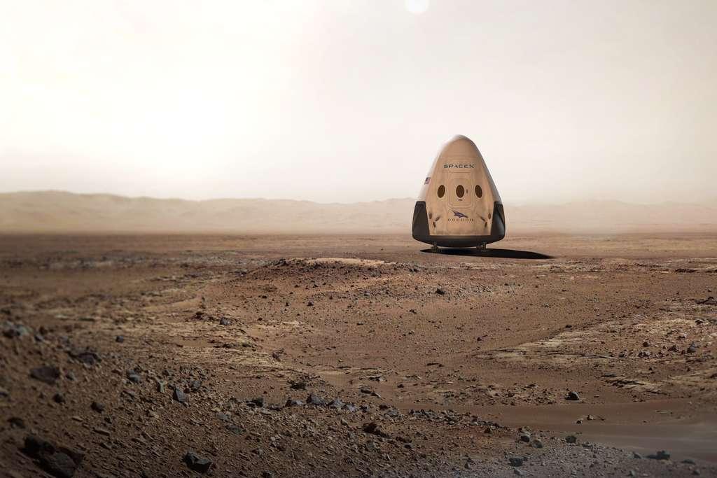 Vue d'artiste d'une capsule Dragon sur le sol martien. En 2018, une version dérivée de la capsule qui ravitaille la Station spatiale sera adaptée aux contraintes d'un voyage entre les deux planètes. Ce ne sera pas ce modèle qui sera utilisé pour la première mission habitée. Il s'agira vraisemblablement d'un véhicule à plusieurs modules dont un, sera gonflable. © SpaceX