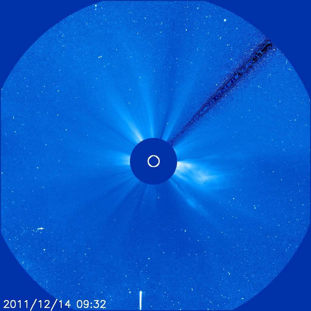 Une photo du Soleil prise derrière le coronographe de Soho le 14 décembre 2011 à 10 h 32 en heure française : la traînée blanche en bas de l'image est la trace de la comète Lovejoy, en train de s'approcher du Soleil, qu'elle devrait raser demain à 140.000 kilomètres avant de s'en éloigner... à moins qu'elle ne sorte pas du piège ! © Soho