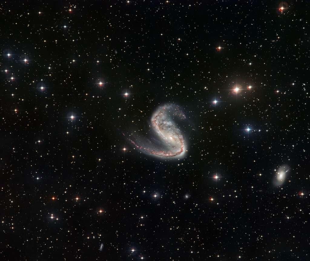 Ce plan large de la galaxie de l'Hameçon réalisé par le télescope de 2,2 mètres de diamètre de l'ESO permet de découvrir le champ environnant ainsi que la dissymétrie qui frappe les bras de NGC 2442. © ESO