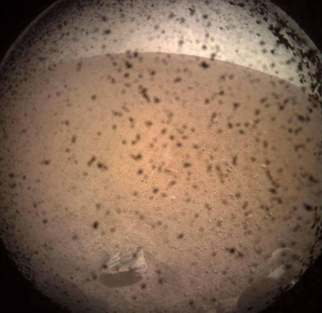 Première image de la surface de Mars acquise par le lander InSight seulement quelques minutes après son atterrissage. Le paysage est certes saturé, mais il s'agit de poussière soulevée lors de l'atterrissage du lander. Elle finira par retomber. @ Nasa, JPL-Caltech